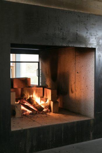 暖炉は正面も背面も壁がなく、両側から火を眺められる。