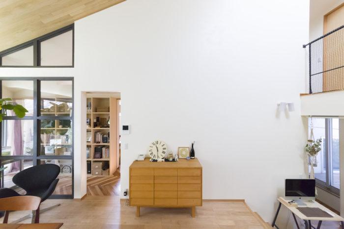 左側の内窓のフレームは、木材を黒く塗装したもの。奥が本棚を設置したホール。北欧雑貨が控えめに飾られている。