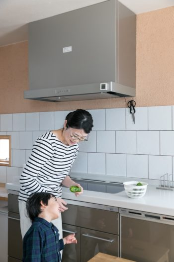 キッチンの壁は、下半分がタイル貼り、上半分が暖色系の漆喰塗り仕上げ。
