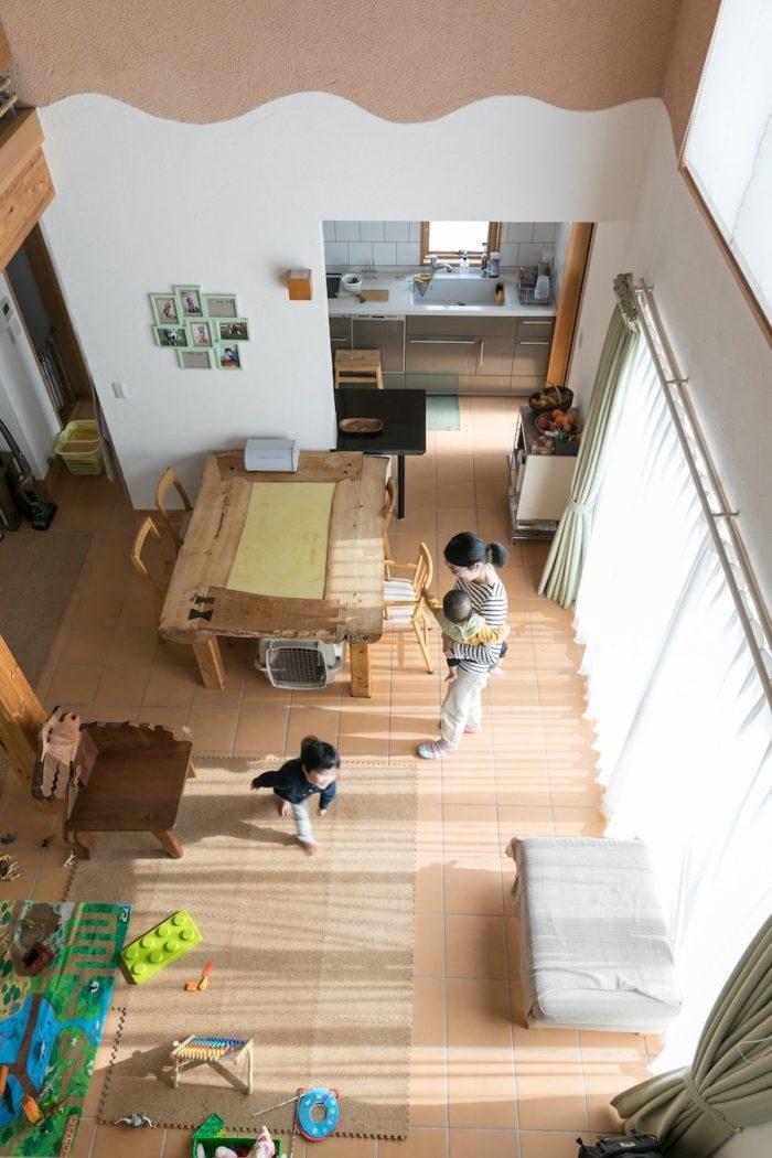 2階からダイニングキッチンを見下ろす。手前が玄関になっている。大きなダイニングテーブルは恵理さんのお父さまがつくったもので、センターの黄色い部分は左官仕上げになっている。