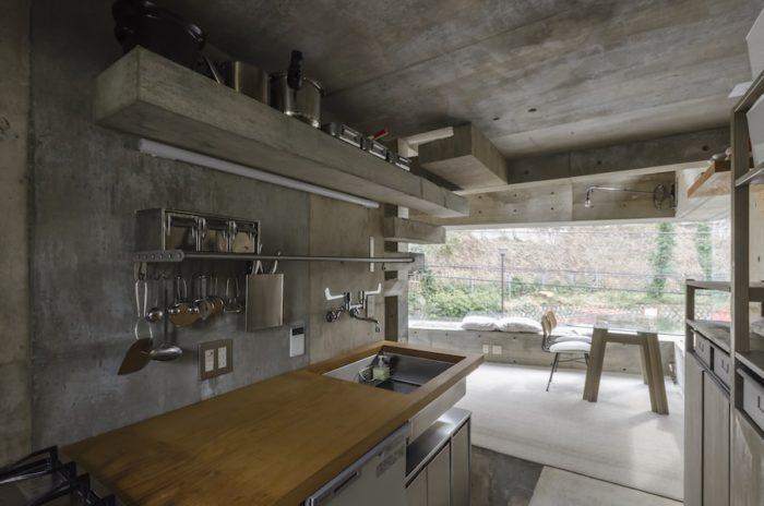 キッチンの天板は実験的にムクの木を使用。グレー1色の空間の雰囲気をこの木の色が和らげている。