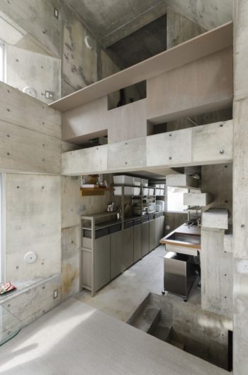 2階のリビングダイニングからキッチン方向を見る。上部のラワン合板はグレーに塗っている。