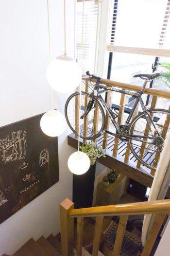 階段から1階玄関を見下ろす。バルコニーに面したスペースの手すりに自転車をディスプレイ。