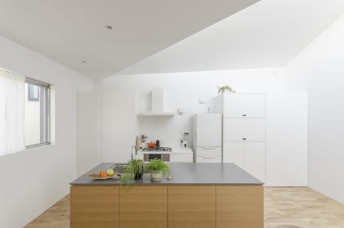 アイランドキッチンの天板はグレーの大理石。これに合わせて下部のナラ材が選択された。背後の収納部分などが真っ白なのはこのキッチン部分を引き立たせるため。