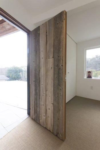 仕事部屋にはサイザル麻を敷いた。古材を使ったドアを開けると、1階とは思えない開けた景色が広がる。