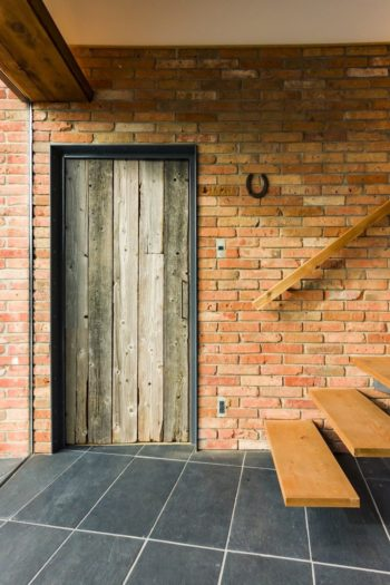 1階の個室のドアは、木製の電柱を薄く切って10年間雨風にさらした材料で作られている。