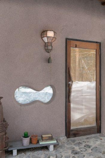 ゲストハウスの玄関。雲のようなかたちに開口部がつくられ、ガラスがはめこまれている。