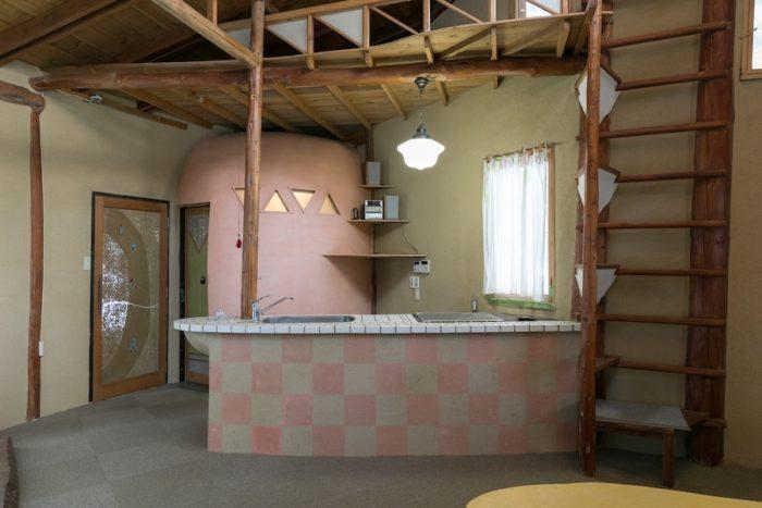 和室からキッチンを見る。リビングダイニングは全面にパイプ式の床暖房が設置されており、暖かい。奥のピンクの円いスペースはトイレ。右手のはしごは、ロフトへ続く。
