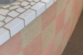 キッチンカウンターの市松模様は、土を塗ってからていねいに色を塗り分けた。カウンタートップはモザイクタイルを貼って仕上げた。大きなタイルを割って一つ一つ貼ったため不揃いなかたちが味になっている。