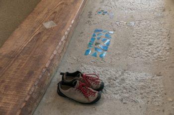 和室とリビングダイニングの間の土間は、タタキふうの洗い出し仕上げ。淡路の瓦や鮮やかな色のタイルを埋め込んでいる。框に使った古材は櫓に使われていたマツで、ボルトがあったところに石をはめこんだ。