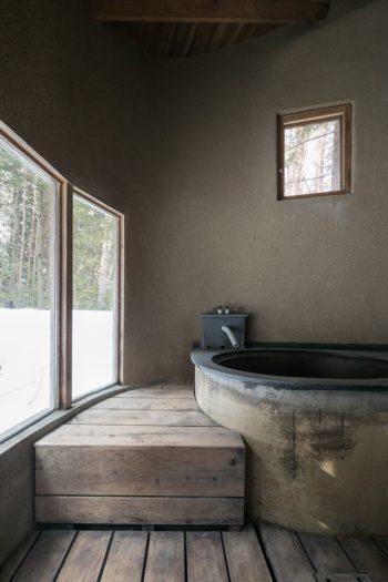 五右衛門風呂。大きな窓から外を眺めながら入浴できる。壁は濡れても大丈夫なモルタル石灰の掻き落とし仕上げ。