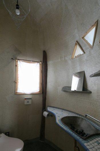 トイレは包み込まれるような円形の空間。手洗いボウルには、紹興酒の甕を縦に切ったものを使っている。