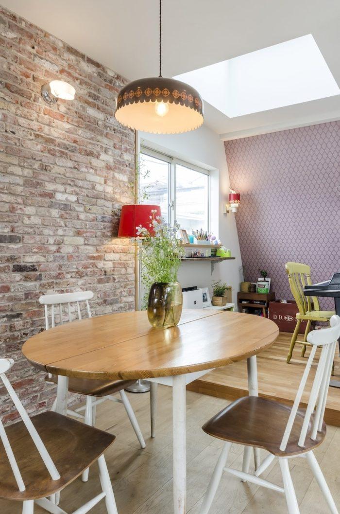 壁のレンガはオランダから取り寄せた古材、テーブルの上の照明は70年代のデンマークの製品で、奥の斜めの壁に貼られた壁紙ともしっかりとコーディネートされてコージーな雰囲気をつくり出している。