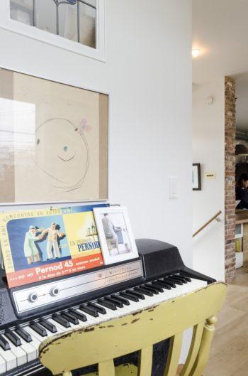 Hさんが時々演奏するという楽器の上には、娘さんが小さいころに描いた絵がかけられている。