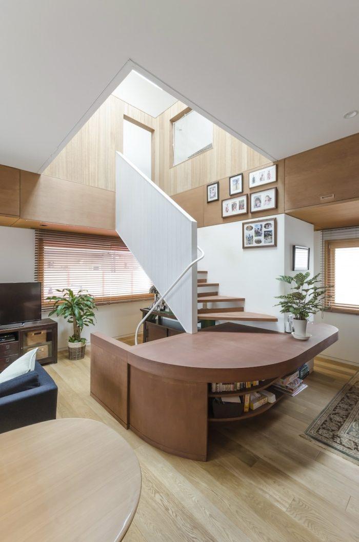 単なる移動のためのスペースではなく、デザイン的な見せ場ともなっている階段部分。色の変化も目を楽しませてくれる。踊り場の下部には本などを収納することができる。
