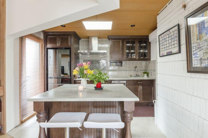 奥さんがこだわったキッチンスペース。壁のタイルもお気に入りのものを選んだ。アイランドキッチンの向きははじめダイニングと平行だったが使い勝手を考えてキッチンと平行になるよう変えてもらったという。