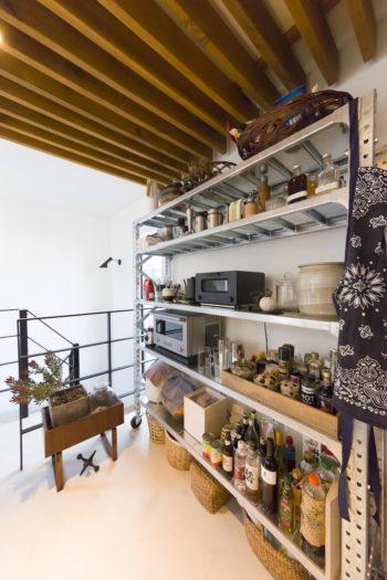 ステンレス製のDULTONの棚に、〈バルミューダ〉のトースターやオーブンレンジ、土鍋、調味料などを収納。