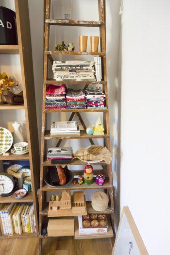 アンティークの脚立を棚として使っている。本やバンダナ、キャンドルなどをリズムよく並べる。
