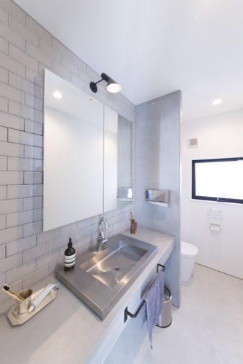清潔感のあるステンレスの洗面ボウル。ライトはヤコブセンのものをチョイス。鏡の裏は収納棚になっている。
