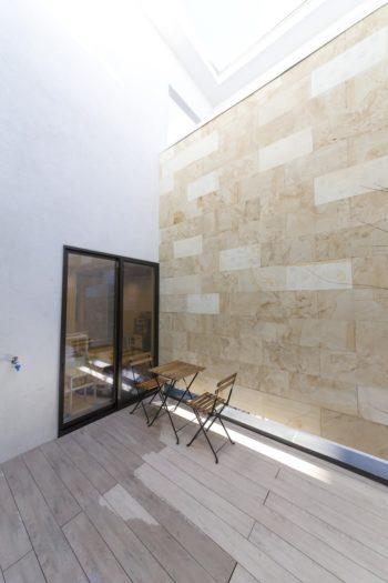 中庭の正面の壁面には天然石のクインを使用。地層のようなマーブル模様とやさしい色合いがリゾート感満載。