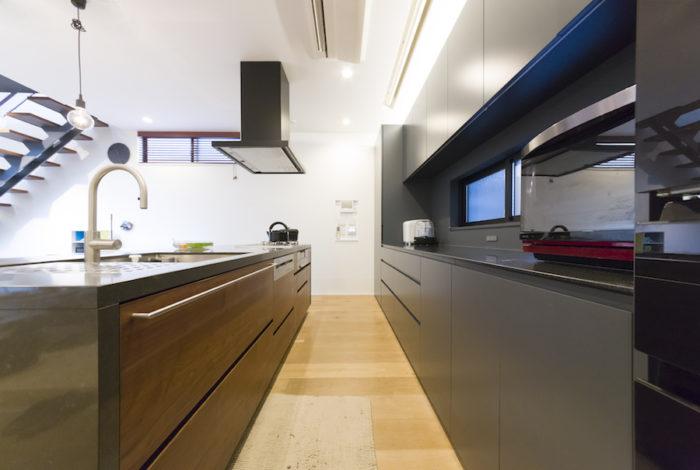 ウォールナットとグレーの落ち着いた配色のキッチン。生活感を出さないようにゴミ箱など全て収納。