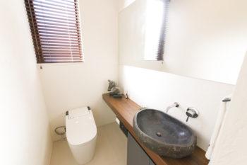1階トイレ。漆喰の壁にウォールナットのカウンターが映える。天然石の洗面ボウルは一点もの。