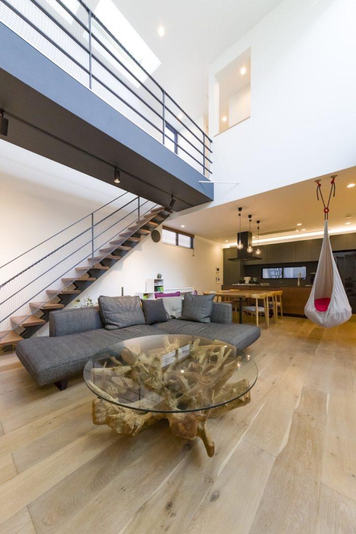 リビングの大胆な吹き抜け。「リビングの中に階段を設けたかった」と軽やかなストリップ階段を設置。古木の脚がインパクト大のガラステーブルは「Kaja」のもの。