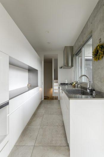 リビング側からキッチンを通して階段を見る。床のタイルは夫婦で選んだもの。