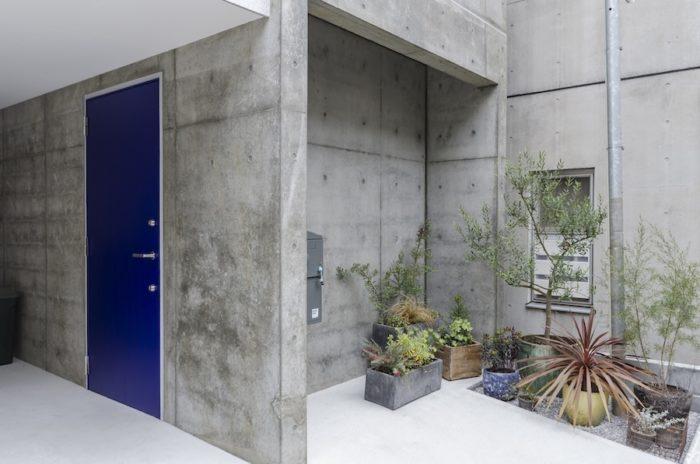 左が「インター・ナショナル・クライン・ブルー(IKB)」が塗られた玄関ドア。道路側にはグリーンがとても感じよくまとめて配置されている。