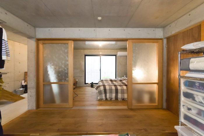 すりガラスを介して、光がベッドルームを通り抜ける。コンクリート、ガラス、オークのシンプルな素材で統一。