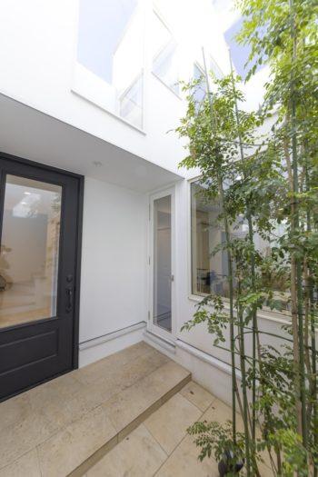 奥のドアから1階のアトリエに直接出入りすることができる。左のドアからはプライベートゾーンへ。玄関ドアは断熱性の高いグラスファイバー素材を採用。