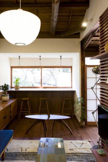 庭の梅や桜、紅葉を見ながらホッと一息つけるカウンターテーブルを窓際に作った。ユニット式のキャビネットはR.J.カイエットのデザイン。対のローテーブルは日本の『KOMA』のpick set table。