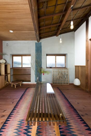 大工だった祖父が作ったベンチにガラスの天板を載せ、ローテーブルに。「玄関に置かれていたものです。」イランのキリムを敷いた。