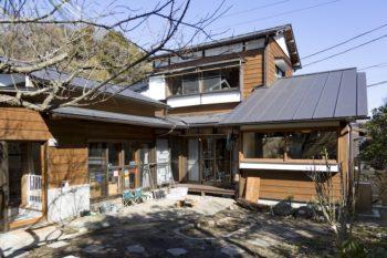 外壁はもともとの建物の雰囲気を残しながら、杉板と漆喰塗りのコンビネーションで仕上げている。左手に保育園の玄関がある。