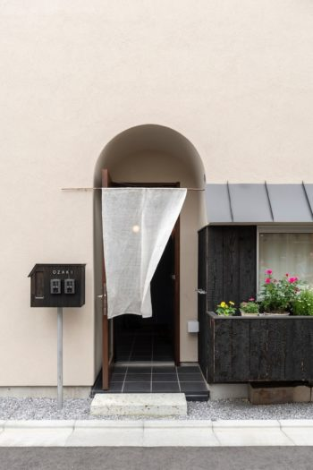 風にたなびく暖簾が無表情な街並みに趣きを与えている。玄関ドアは壁面より後退した部分に配されている。