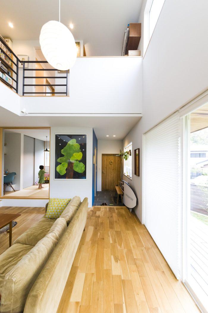 5mを超える天井高の吹き抜けが気持ちいい。ゲストルームを兼ねた小上がりは、畳の下が収納になっている。2階に仕事部屋と寝室がある。ブルーの壁は黒板塗装。壁に飾った木と夜空の絵は、秋山花さんの作品。玄関に置いてあるのはパドルボード。「SUP(スタンドアップパドルボード)は葉山に越してから始めました」