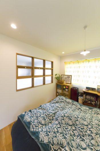 寝室の模様ガラスの飾り窓は吹き抜けに面している。ベッドのマットレスは、妙子さんが仕事をしている地元葉山の「ボディドクター」のものを使っている。
