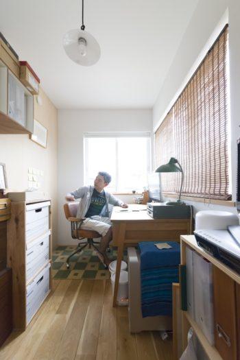 謙治さんの仕事スペース。後ろの壁に貼ったポストイットを振り返ってチェック。バンカーズボックスを収めた棚は謙治さんのDIY。