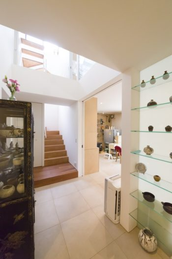 玄関から吹き抜けホール、アトリエへと続く床は、同じタイルで統一されている。2階の生活の場に続く階段からはあたたかみのあるフローリングに。アトリエと住居空間で気分を変えている。