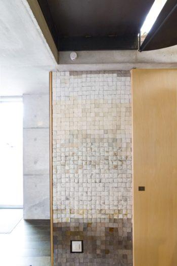 1階のエントランスホールの階段スペースの正面に、陶芸家である妻の作品が。1枚ずつムラのある色合いが味わい深い。