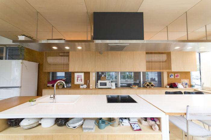 白いタイル貼りのキッチンはオーダーで造作。キャスターを付け、シンクの配管もフレキシブルにして移動を可能にした。シンク下には収納も設けた。