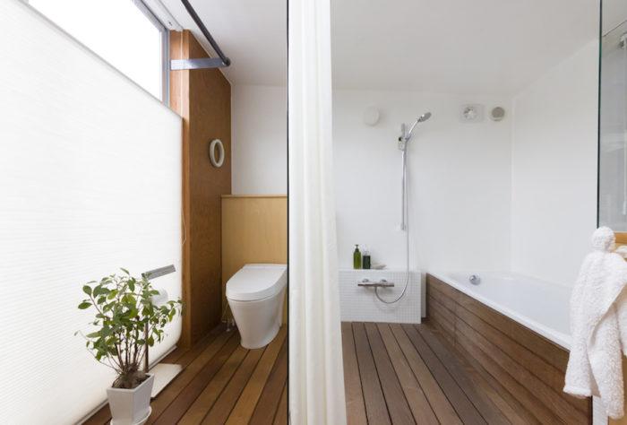 南洋の腐りにくいイペという木をすのこ状にして敷き詰めたバスルーム。壁や天井は耐久性の高いFRP防水で仕上げた。シャワーカーテンを開けておけば、お風呂とトイレの間の強化ガラスを光が通り抜ける。