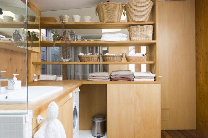 真上にトップライトを設置した洗面。洗濯機をビルトインできるようカウンターを造作。その上でアイロンをかけたり、窓際に洗濯物を干したり。家事動線もよい。