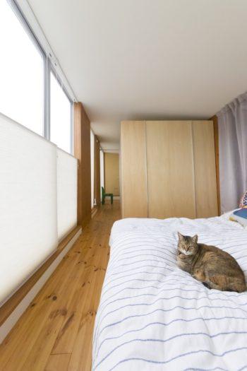 日溜まりのようなベッドの上は愛猫もお気に入り。間仕切りにもなっている入り口の収納も、キャスター付きの可動式。