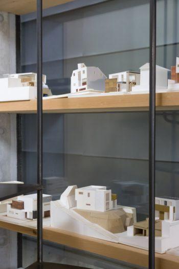 壁の厚みを利用した階段脇のスペースに、これまでに手がけた家の模型を飾る。