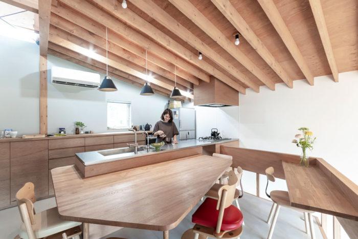 奥さんのご両親がよく訪れるため4人家族にしては大きなテーブル。2人並んで作業ができるようにキッチンも大きくした。キッチン部分の壁はグレーにして落ち着いた雰囲気に。吊戸棚をつくらなかったためすっきりとした壁面になっている。