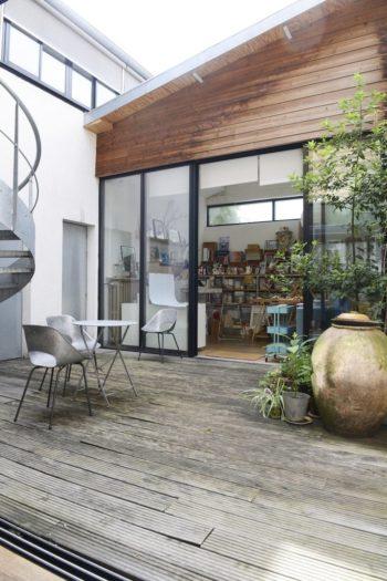 玄関を入ってすぐ、ギャラリー兼リビングからの眺め。中庭の先がアトリエだ。