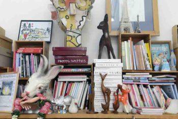 アトリエの棚にはキッチュな人形やオブジェがそこかしこに置かれている。