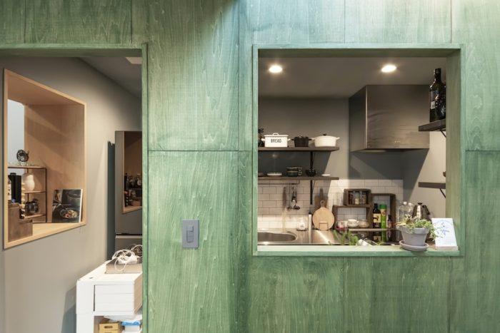壁面が緑に塗られたキッチン。出入口のほかに吹き抜けとダイニングに向かって開口が開けられている。