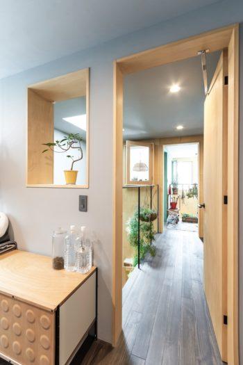 寝室から見る。出窓を通して、寝室、吹き抜け、和室と空間が3層通して見える。